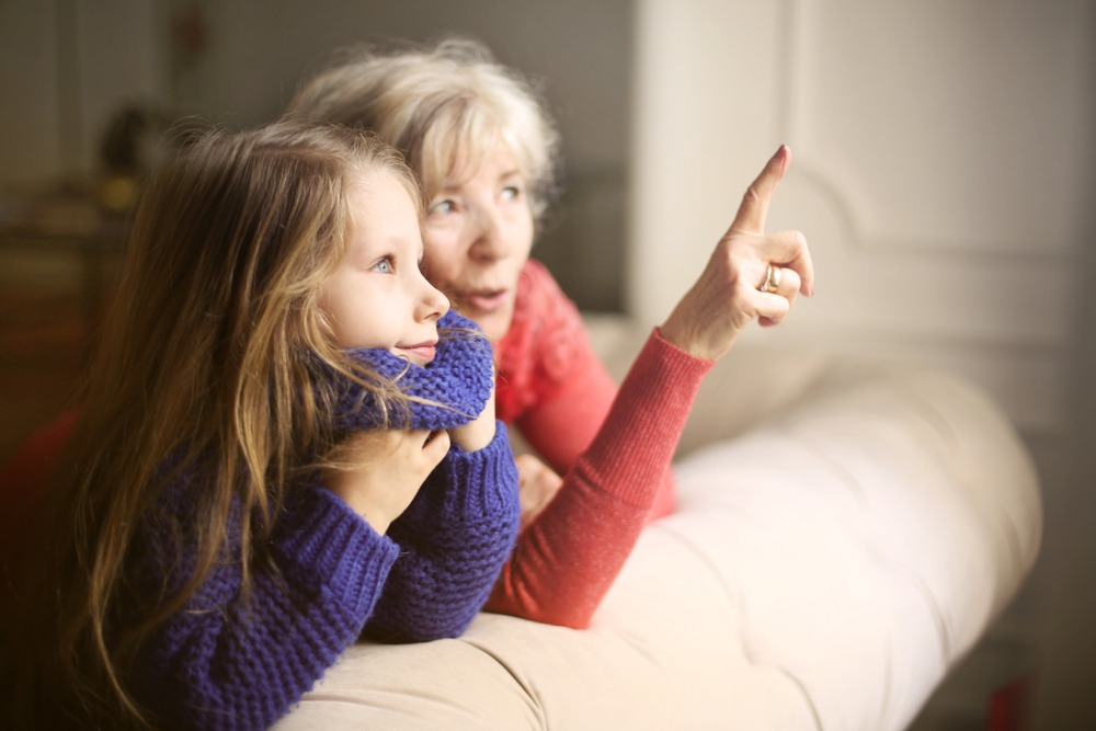Young girl in a purple sweater sitting next to her grandmother who is pointing at something outside.