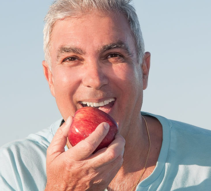 mature adult man wearing dentures eating apple