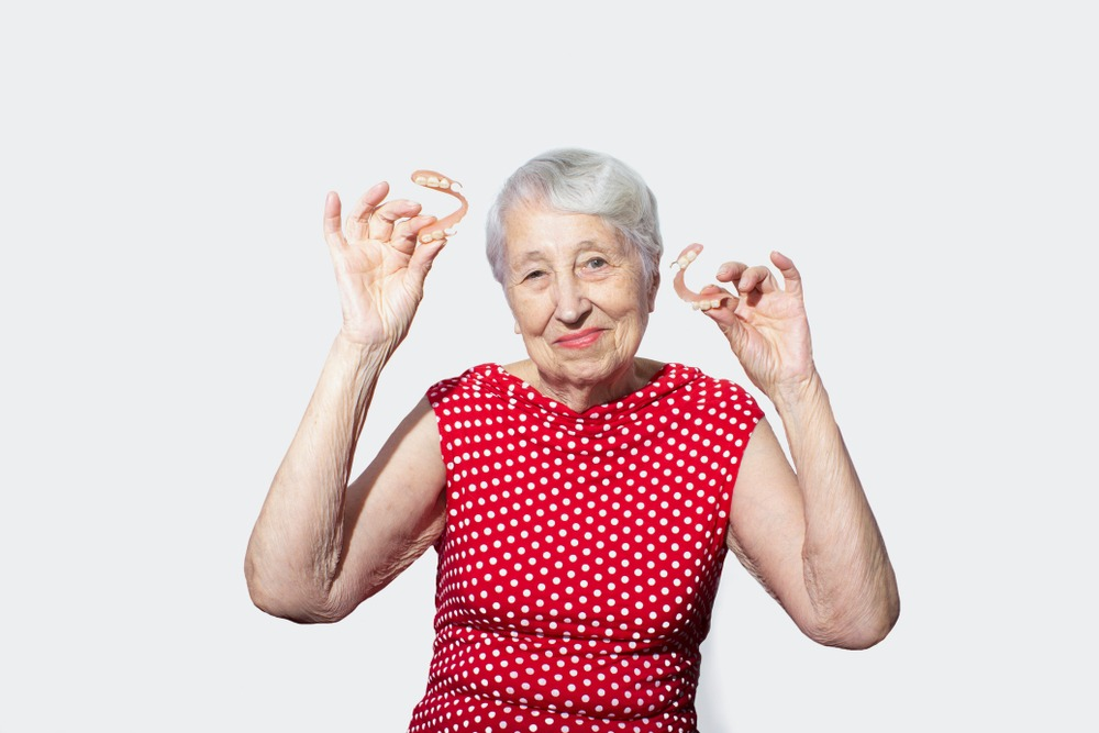 mature woman holding dentures