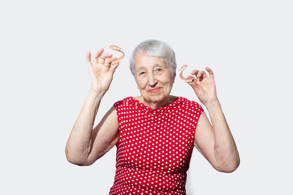 mature woman holding dentures