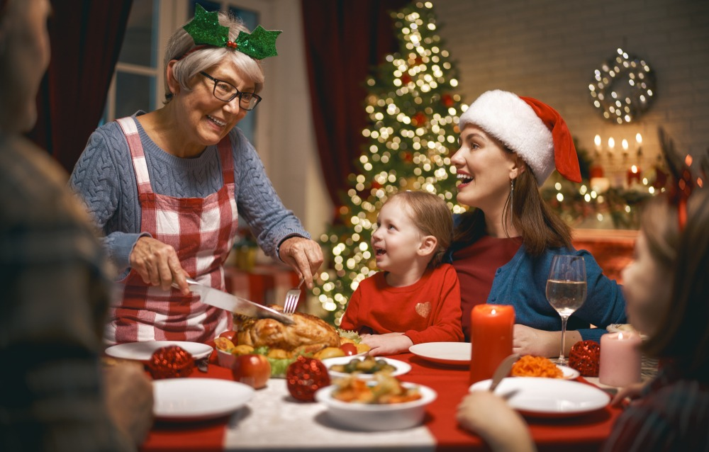 senior woman with dentures serves xmas dinner to family