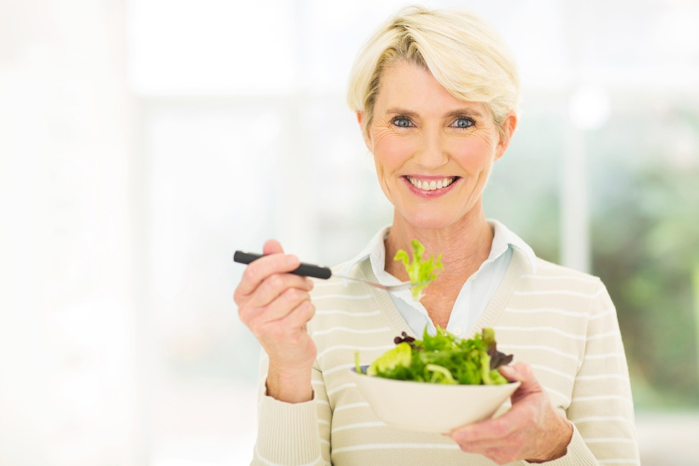 mature woman with dentures smiling while eating salad