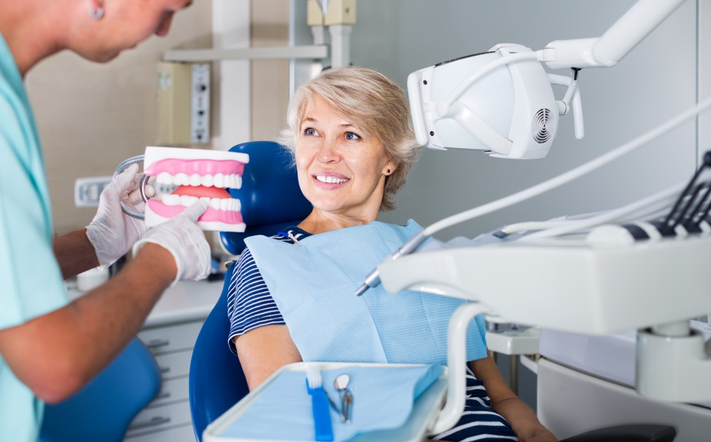 Middle aged woman in a dental chair being shown a denture model.