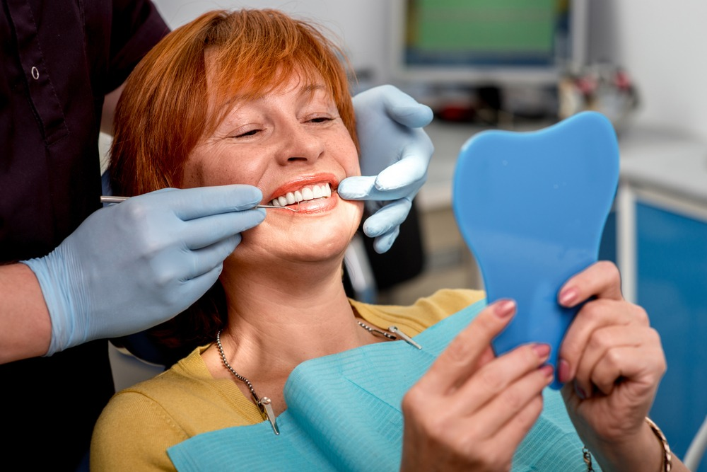 Older woman in a dental chair checking out her new dentures in a mirror.