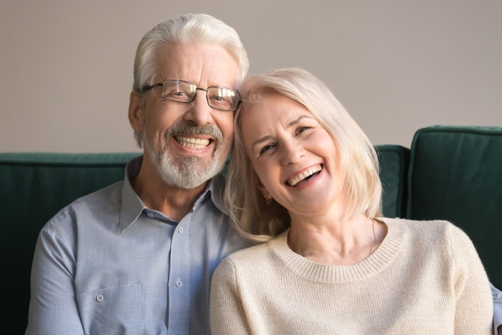 Older couple with dentures sitting on a green couch smiling.