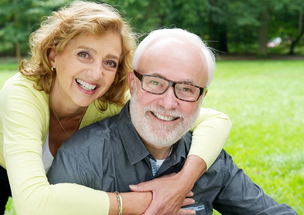 Older couple with dentures sitting in a park smiling.