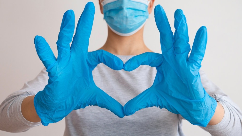 denture clinic staff wearing a mask and making a heart shape with gloved hands.