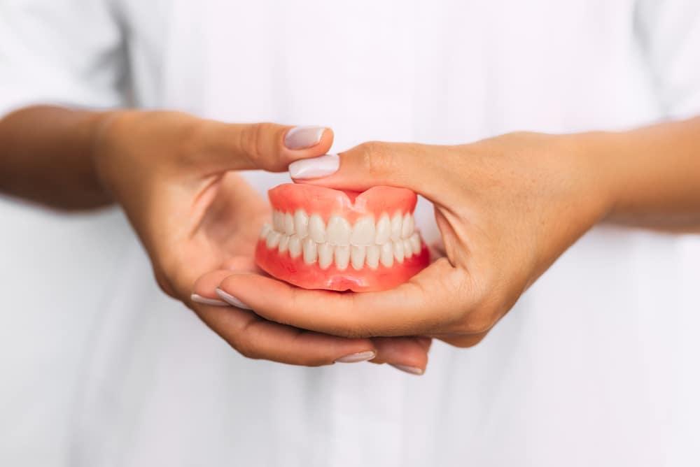 Denture clinic staff holding complete dentures.
