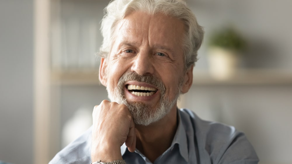 mature man with dentures smiles