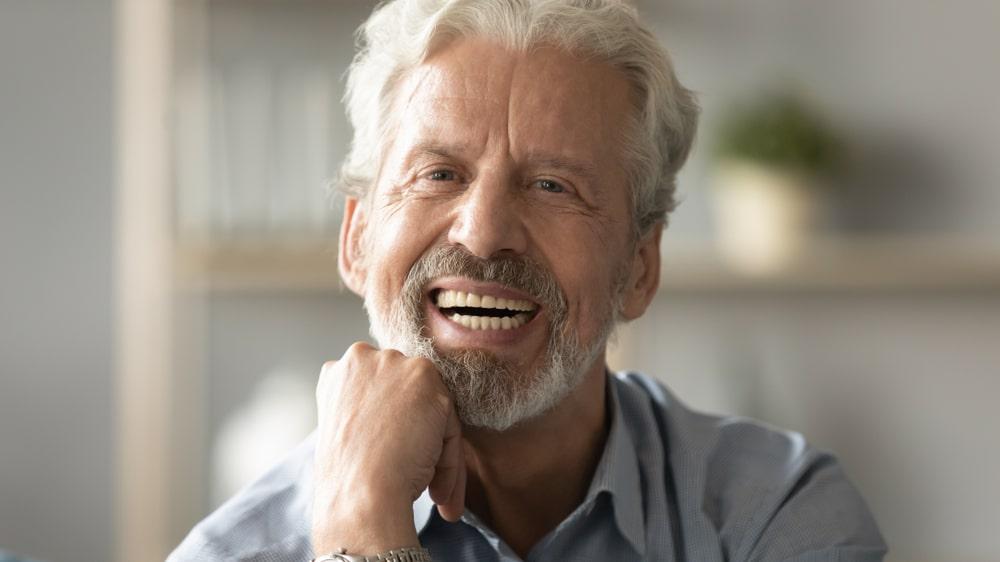mature man with dentures smiles