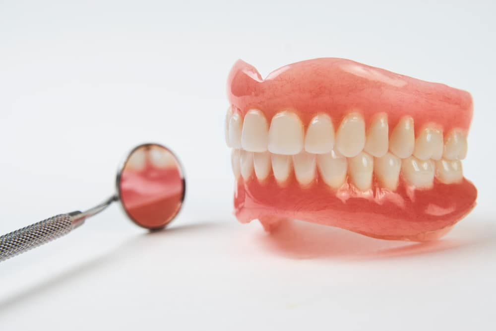 New set of complete dentures beside a dental mirror.
