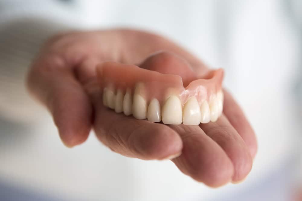 denturist holds dentures in hand