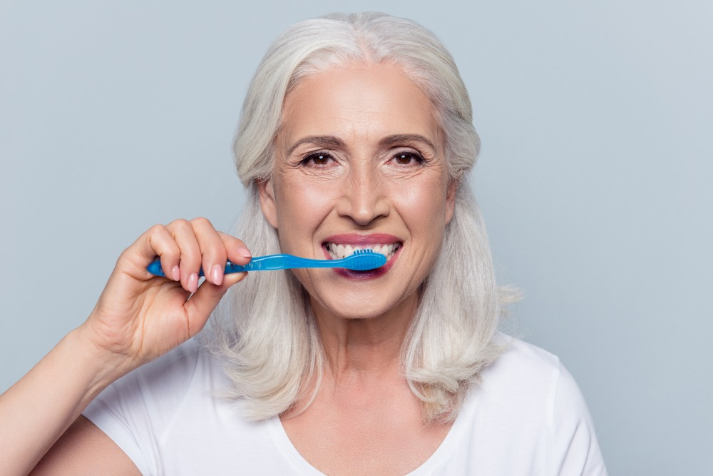 Older woman brushing her dentures with a blue toothbrush