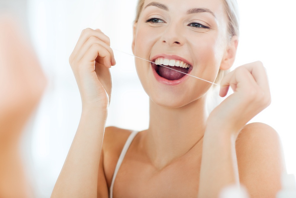woman flossing teeth for oral health