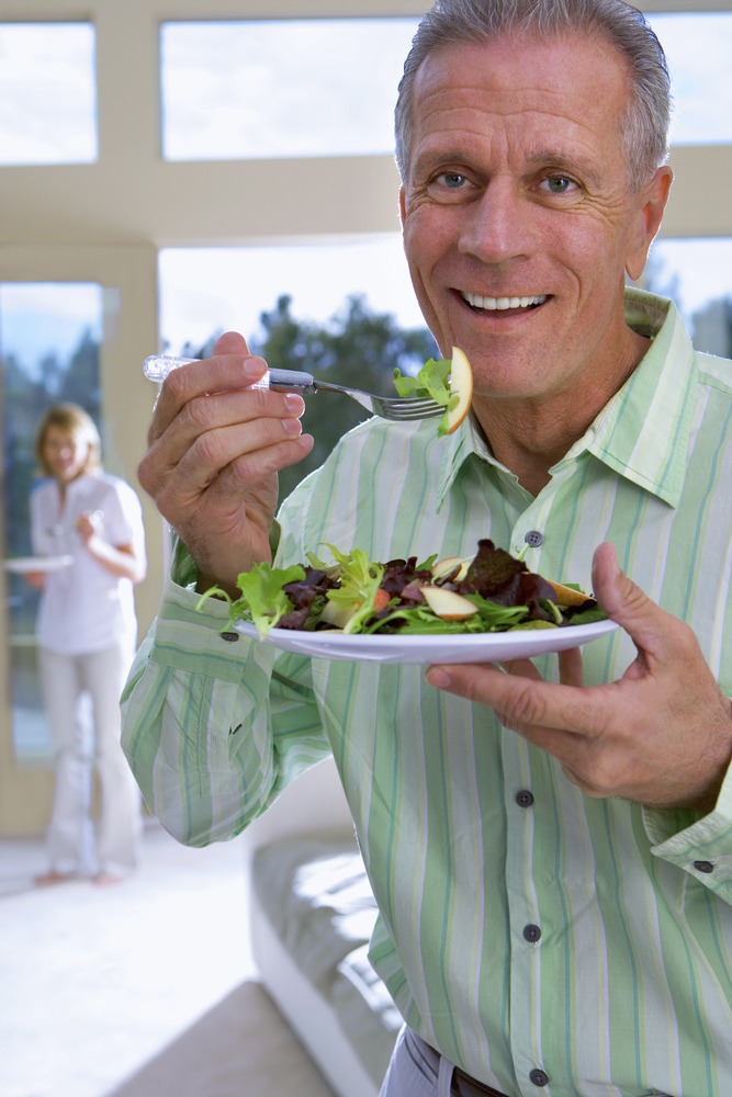 senior man eats meal with family