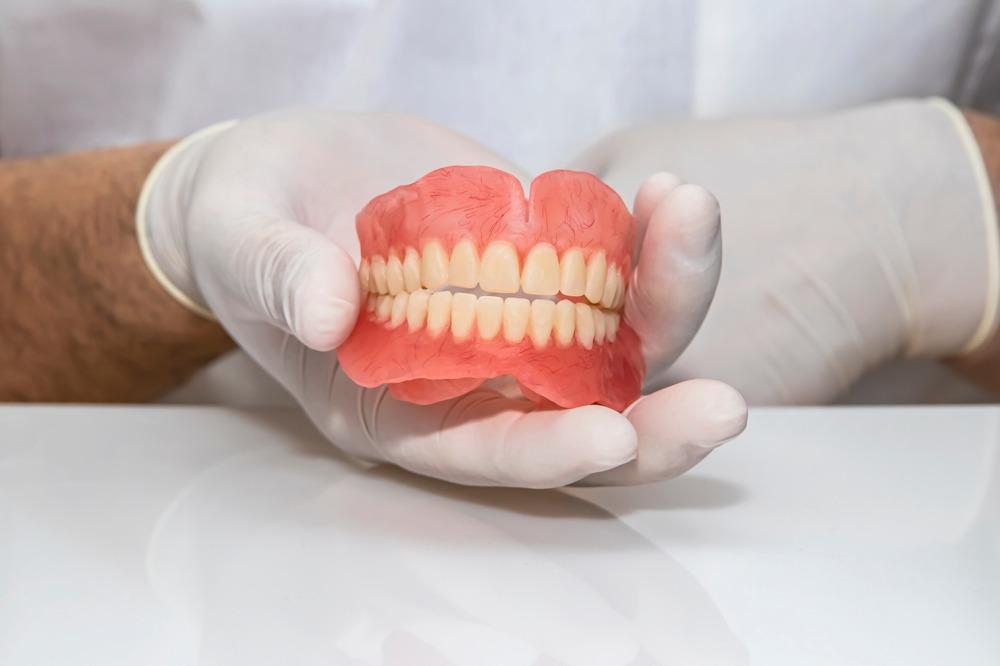denturist holding set of digital dentures