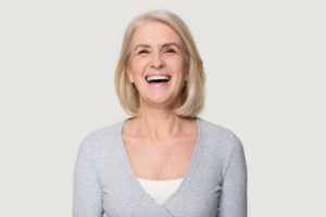 woman smiling with visible denture implants