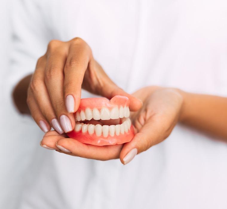 a denturist holding a set of dentures